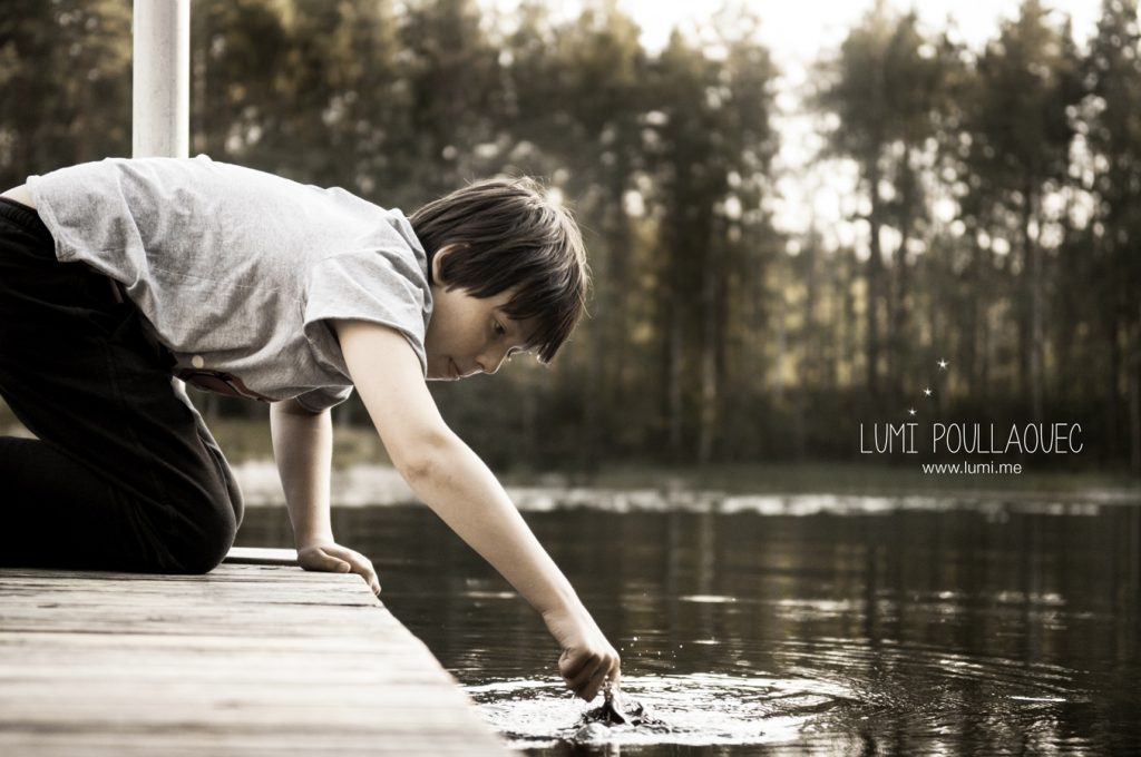 Photographie d'un jeune garçon autiste jouant au bord d'un lac.